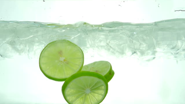 Lime slices drop in the ice water. Close up. Slow motion.