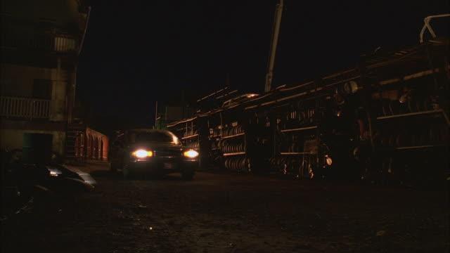 CS WS PAN Limousine driving through junkyard at night