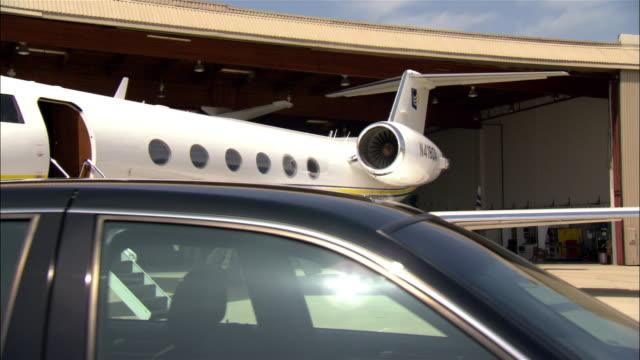 WS DS Limousine near private airplane outside hangar at airport / Long Beach, California, USA