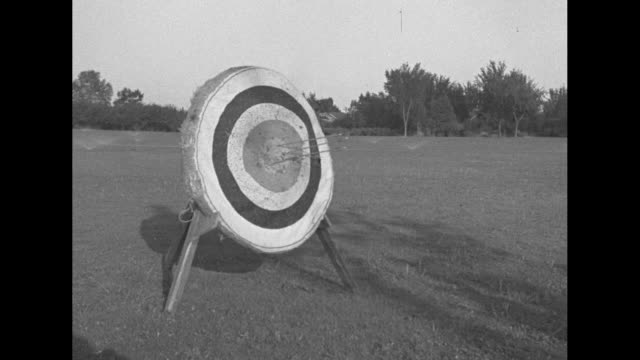 VS line of archers shooting and hitting targets / James Lynch leans down next to target to have a cigar shot out of his mouth / Peter Moser kisses...