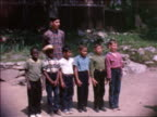 1964 line of boys standing still with teen camp counselor standing behind them / home movie
