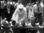 B/W 1932 line of boys stuffing faces in pies in pie eating contest / crowd watching in background