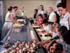 1960 line of children + teachers being served food + beverages on trays in school cafeteria