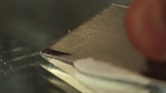 ECU SELECTIVE FOCUS Line of cocaine being sorted with razor blade / Los Angeles, California, USA