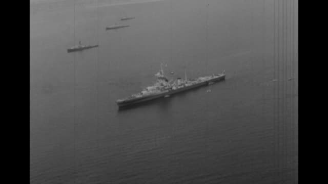 AERIAL line of European navy ships conducting maneuvers off coast of Brittany wing of camera plane in foreground / AERIAL line curves as ships turn /...