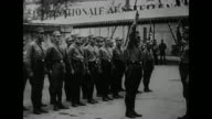 Line of German military personnel possibly Brown Shirts looks on as one man steps forward issues Nazi salute to superior turns smartly and walks back...