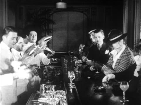 B/W 1928 line of people sitting at bar as line of bartenders use cocktail shakers / newsreel