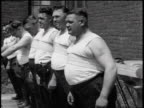 B/W 1935 line of policemen in tank tops standing with vibrating straps on bellies / newsreel