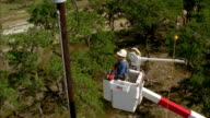 CS SLO MO WS HA Lineman in bucket truck looking up at power lines / Johnson City, Texas, USA