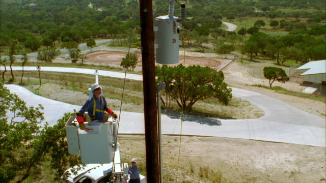 CS SLO MO WS Lineman in bucket truck looking up at power lines / Johnson City, Texas, USA
