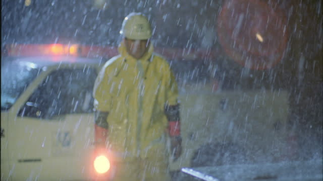 SLO MO MS Lineman walking from truck to ground transformer in pouring rain / Cedar Park, Texas, USA