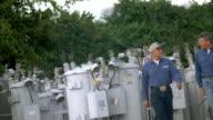 SLO MO MS PAN Linemen walking through substation and chatting / Johnson City, Texas, USA