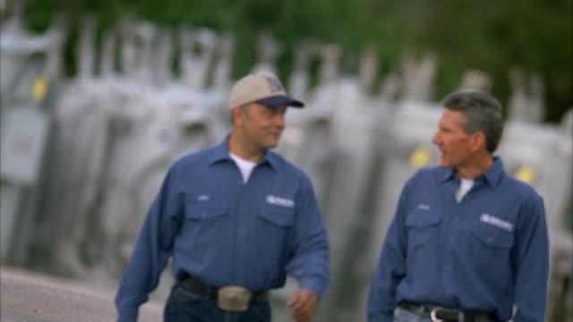 SLO MO MS PAN R/F Linemen walking through substation and chatting / Johnson City, Texas, USA