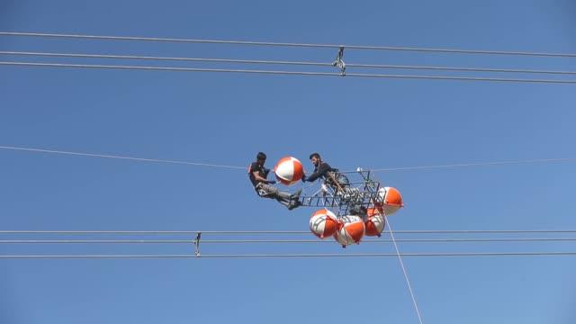 Linemen work at the construction of new highvoltage transmission line between Siirt and Van provinces in eastern Turkey on October 08 2017 Lineman...