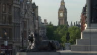 WS Lion statues in Trafalgar Square with Big Ben in background / London, England