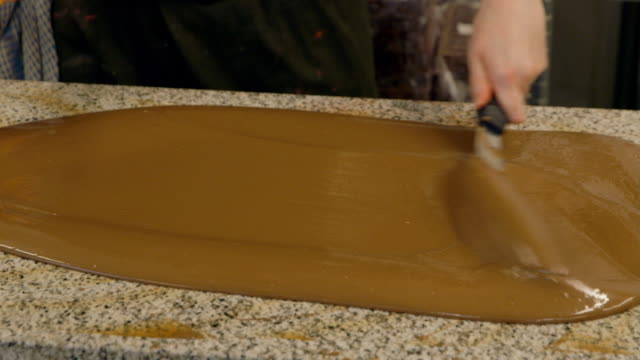 Liquid chocolate being spread and mixed with a spatula on a stone worktop