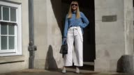 Lisa Aiken wears sunglasses a blue top with flared sleeves white flared pants outside Simone Rocha during London Fashion Week September 2017 on...
