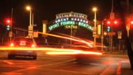 WS Lit archway entering Yacht Harbor blur of traffic on street FG lit Pacific Wheel ferris wheel BG CA