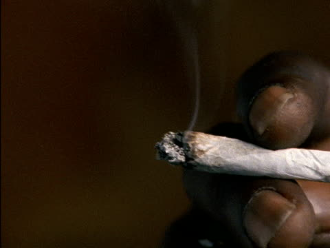 CU of lit marijuana joint man brings it to his mouth and smokes Lit marijuana joint on January 01 1992 in Jamaica