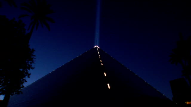 Lit pyramid of Luxor Las Vegas hotel casino the light of Luxor beaming straight up into clear sky silhouette of palm trees around NV Las Vegas...