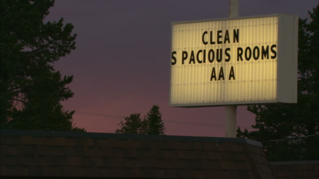 A lit sign advertising motel rooms glows brightly against a dim sky.