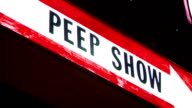 Lit sign w/ letterings Peep Show over white arrow Erotic exotic adult exhibition sex show sexuality