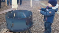 Littel boy (4 years) warms his hands close to the fire of metal container for firing. Smoke comes out of the metal container.