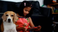 Little african girl using her tablet and her beagle dog looking on tablet