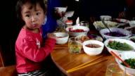 Wenig asiatische Mädchen isst traditionelle Speisen