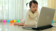 Little asian girl play laptop in home
