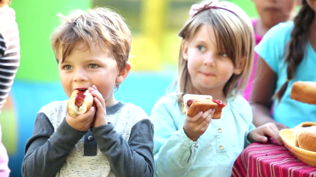 Little boy and girl eating hotdogs