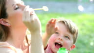 Little boy and mother, blowing bubbles with wand