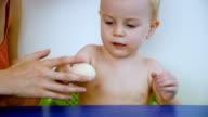 Little boy cleaning boiled egg from egg shell