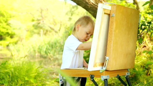 little boy drawing on nature