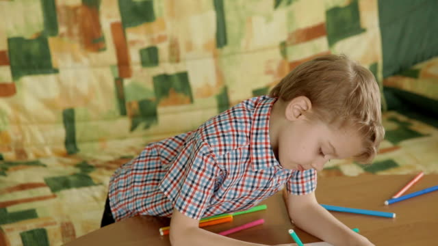 Little boy drawing pictures indoors