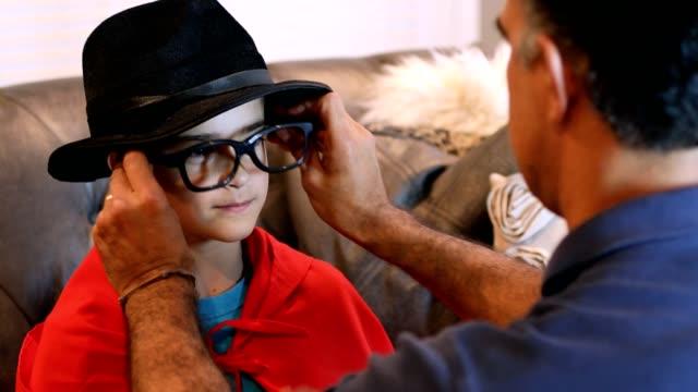 Kleiner Junge verkleidet sich zu Halloween mit Papas Hilfe.