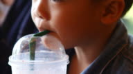 little boy drinking juice through a straw