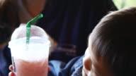 kleiner Junge Saft durch einen Strohhalm zu trinken