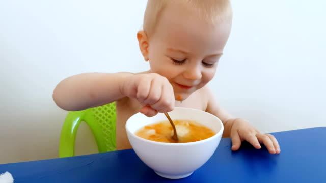 Little boy eating a soup
