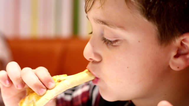 Little boy eating pizza close-up