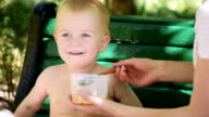 Little boy eating soup outdoors