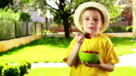 Little boy eating strawberry, showing thumbs up