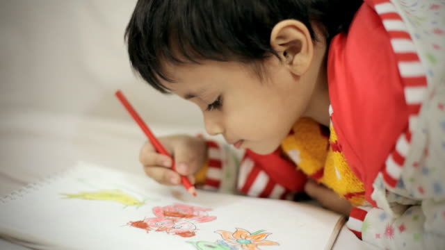 Little boy filling color in coloring book