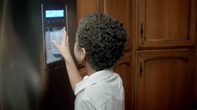 HD: Little Boy getting Water from the Refrigerator