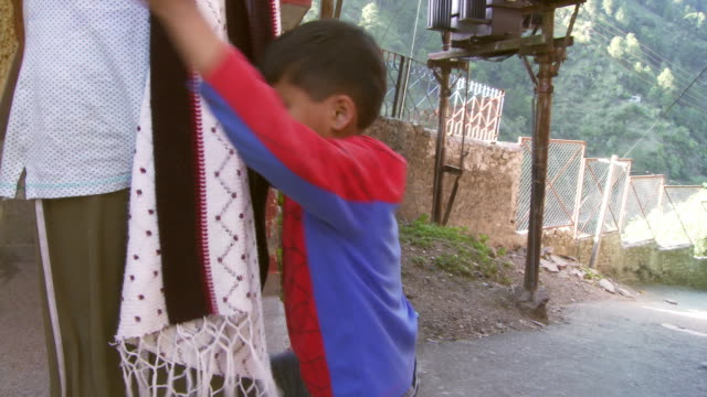 Little boy in spiderman shirt hugging girl who's playing on cell phone