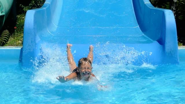 little boy is riding a water slide (slow motion)