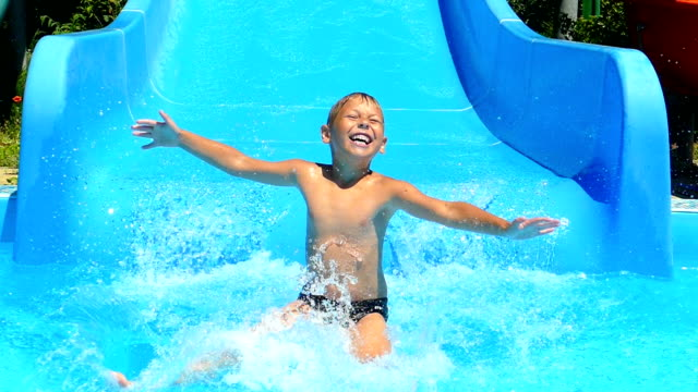 little boy is riding on the water slides of the water park (slow motion)