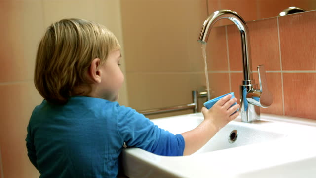 Little Boy Playing With Running Water