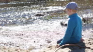 Little boy plays next to the river