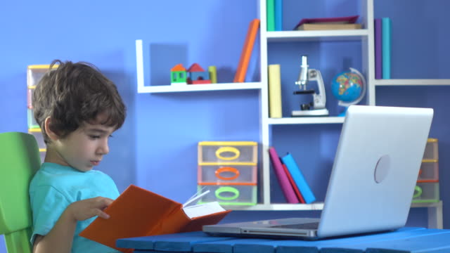 Little Boy Reading Book And Using Notebook Computer